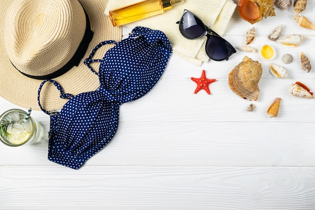Summer beach pool composition with hat sunglasses refershing drink on wood