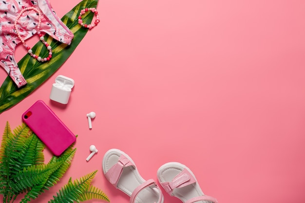 夏のビーチのトップビューのコンセプトの子供たちの夏の服やアクセサリーをピンクの背景にg ...