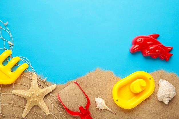 コピースペースと青い背景にアクセサリーと夏のビーチおもちゃ。夏のフレーム
