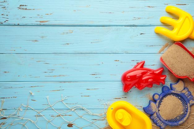 コピースペースと青い木製の背景にアクセサリーと夏のビーチおもちゃ。夏のフレーム