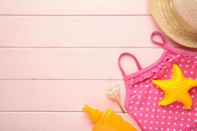 コピースペースとピンクの背景にアクセサリーと夏のビーチおもちゃ。夏のフレーム