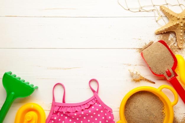コピースペースと白い背景の上のアクセサリーと夏のビーチおもちゃ。夏のフレーム