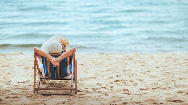 여름 해변 여행 휴가 개념, 모자를 쓴 행복한 여행자 아시아 여성이 태국 촌부리 파타야의 의자 해변에서 팔을 벌리고 휴식을 취합니다.