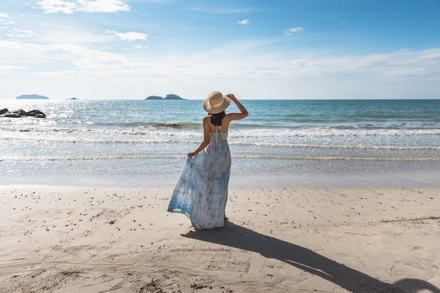 Summer beach travel vacation concept, happy traveler asian woman with white dress relaxing on beach in evening at thailand, vintage style