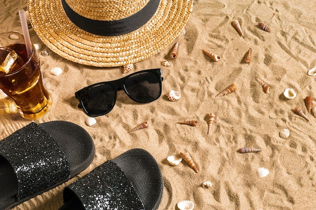 Summer beachwear, flip flops, hat, cold drink in a glass and seashells on sand beach