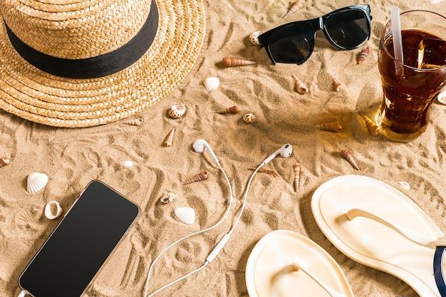 Summer beachwear, flip flops, hat, sunglasses and seashells on sand beach