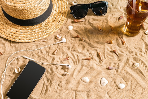 Summer beachwear, sunglasses, hat, cold drink in a glass and seashells on sand beach