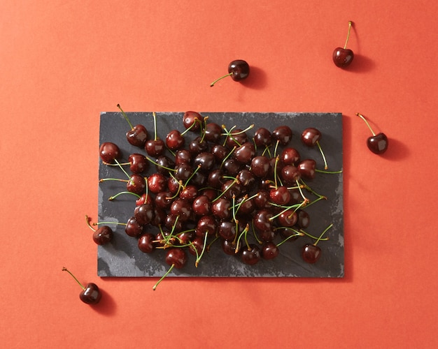 Summer berries background from red ripe cherries on dark stone board