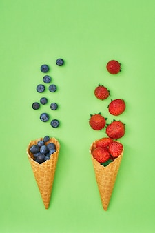 Summer berries in ice cream cone on green background