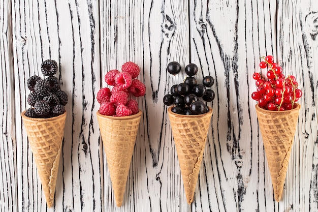 Summer berries in waffle cone on white wooden background