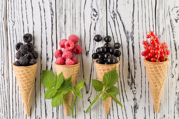 Summer berries in waffle cone on white wooden background.