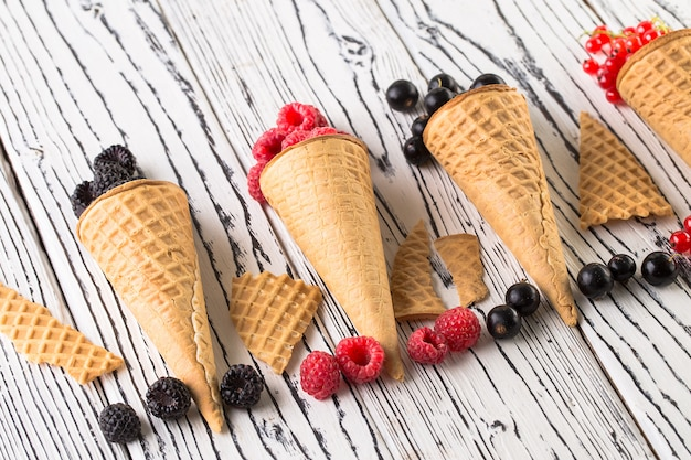 Summer berries in waffle cone on wooden background