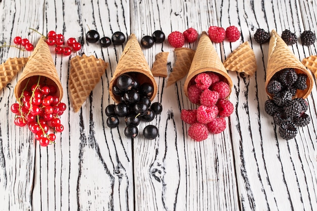 Summer berries in waffle cone on wooden background.