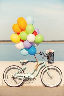 Летний байк. картина старинного велосипеда с воздушными шарами и цветами в корзине