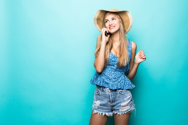 白い背景で隔離の携帯電話を呼び出す麦わら帽子の夏のブロンドの女性