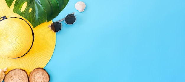 Summer blue banner with yellow hat ,sunglasses,seashell and monstera leaf