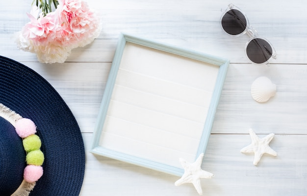 Summer blue female hat and picture frame with sunglasses and seashell decoration on wood table