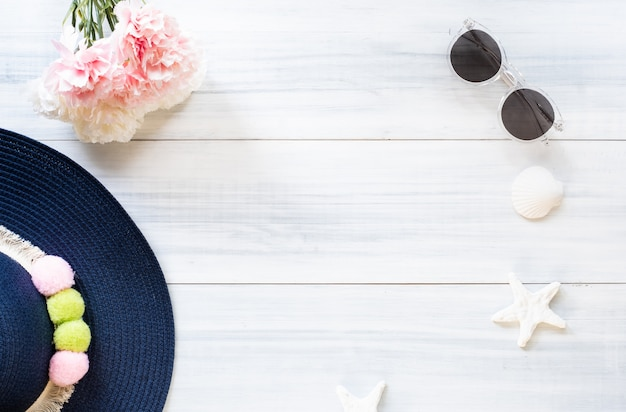Summer blue female hat with sunglasses and shell and star fish decoration on white wood table