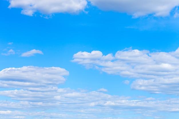 白いふわふわの雲と夏の青い空。水平フレーム