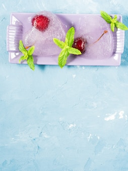 Summer blue textured ice hearts frozen cherries. copyspace