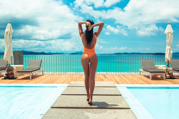 Summer body. woman in orange swimsuit near swimming pool with sea view. girl in fashionable swimwear with perfect body at luxury resort. back view
