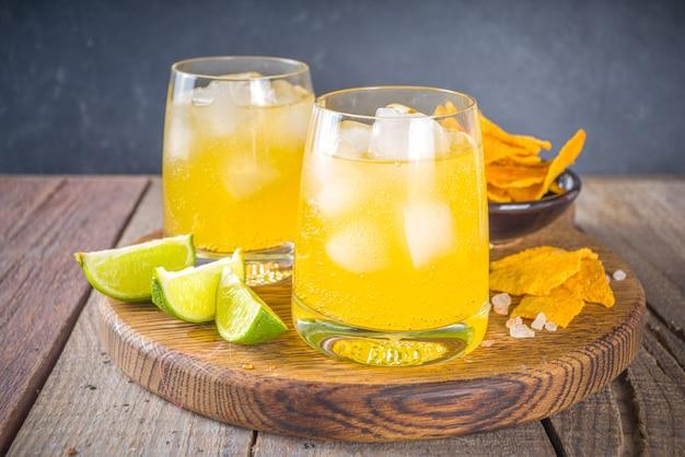 Летний алкогольный цитрусовый коктейль, цитрусовая маргарита, напиток текила с солью и мексиканскими чипсами