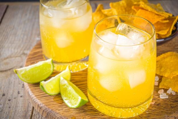 夏の大酒飲みの柑橘系カクテル、柑橘系のマルガリータ、塩とメキシカンチップスのテキーラドリンク