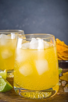 Summer boozy citrus cocktail, citrus margarita, tequila drink with salt and mexican chips