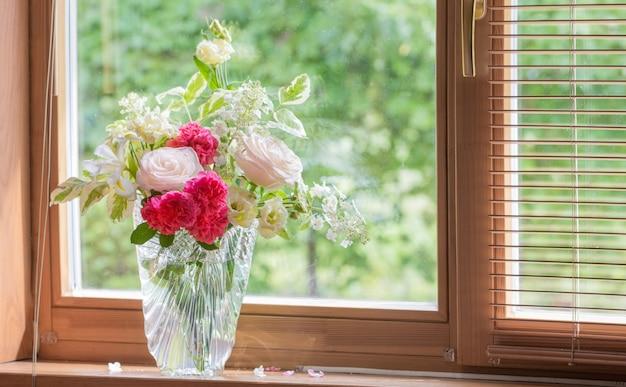목조 주택 창턱에 유리 꽃병에 여름 꽃다발