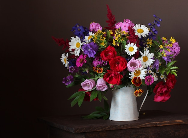 Summer bouquet in a jar: roses, daisies, phlox, bells and other garden flowers