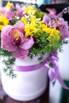 Летний букет из ярких цветов в бумажной коробке. подарок к празднику
