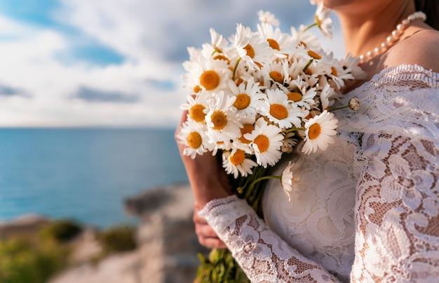 하얀 드레스를 입고 신부 손에 필드 데이지의 여름 꽃다발. 바다의 배경에 따뜻한 일몰 시간. 공간을 복사하십시오. 평온함, 침묵, 자연과의 단결의 개념.