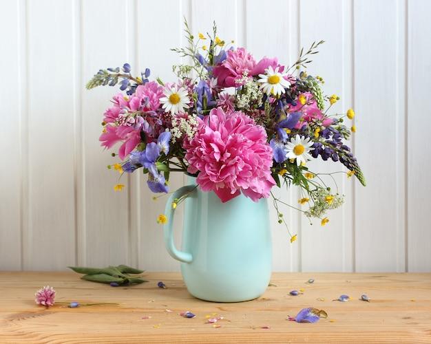 白い背景の上のテーブルの上の夏の花束牡丹デイジールピナスキンポウゲと他の花