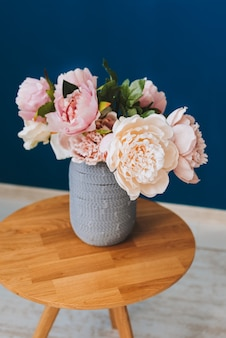 Summer bouquet of pink and blush peonies against blue wall background