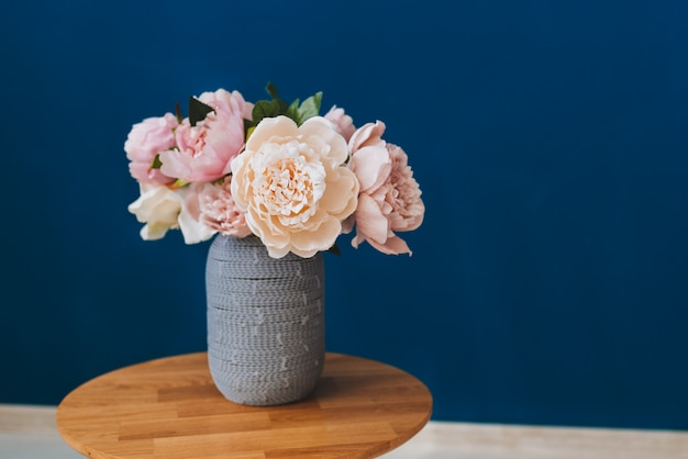 Summer bouquet of pink and blush peonies against blue wall