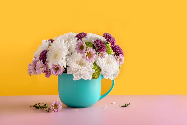 Summer bouquet of white chrysanthemum flowers in a blue cup on a yellow background. summer flower background of chrysanthemum flowers.
