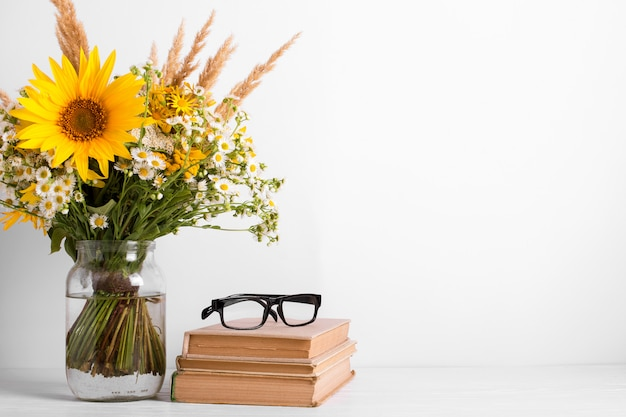 Summer bouquet of wildflowers in glass vase, old books. season design concept. teachers day concept