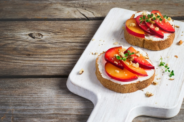 Summer breakfast bruschetta with plums,walnut and cottage cheese