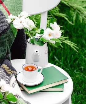 Summer breakfast in garden. cup of tea on books, flowers vase teapot, warm plaid on white chair outside in garden. romantic provence leisure breakfast with nature background.
