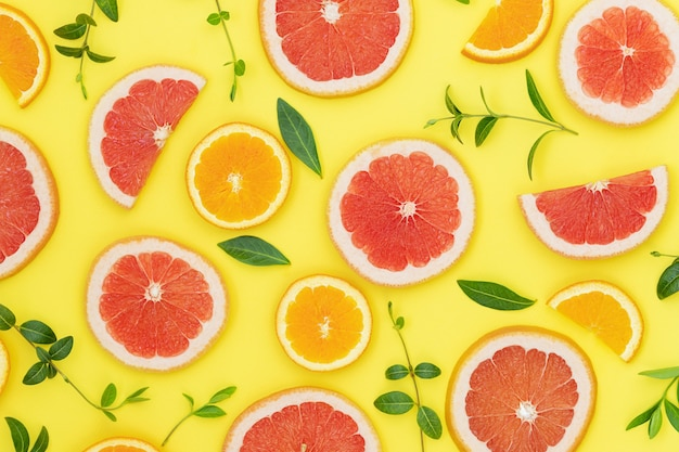 Summer bright background with oranges grapefruits and green leaves on the yellow surface