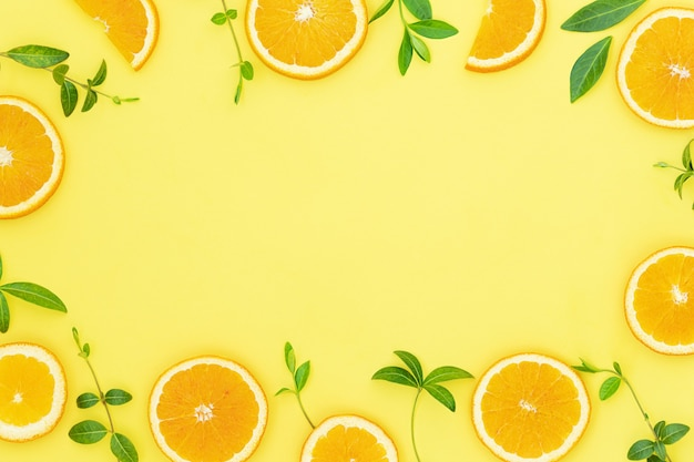 Summer bright background with oranges and green leaves on the yellow surface and place for text in the middle