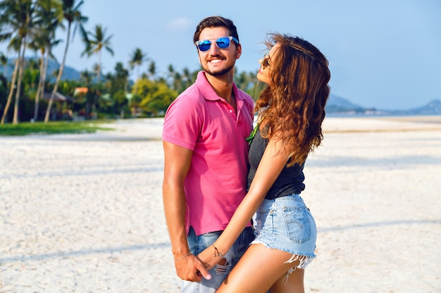 Summer bright fashion portrait of beautiful couple in love, wearing stylish bright casual hipster clothes and sunglasses, holding hands hugs and enjoy their vacation near ocean.
