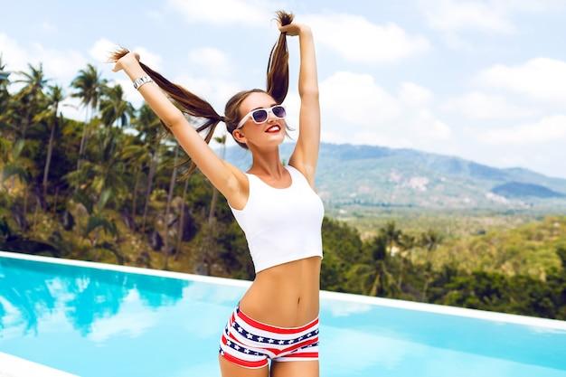 Летний яркий портрет сексуальной хипстерской девушки, развлекающейся на вечеринке у бассейна, держа ее за хвостики и флирта, радости, отпуска, тропического острова.