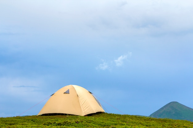 Summer bright sunny day. small tourist tent on grassy valley on distant misty green mountains under clear blue cloudless sky background. tourism, hiking, camping and beauty of nature concept.