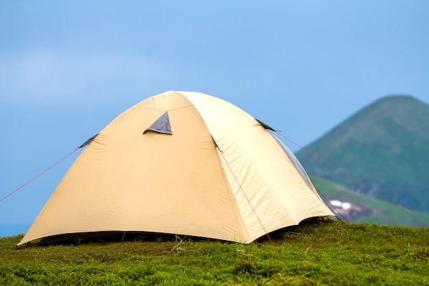 여름 밝고 화창한 날입니다. 맑고 푸른 cloudless 하늘 배경에서 먼 안개 낀 녹색 산에 잔디 계곡에 작은 관광 텐트. 관광, 하이킹, 캠핑 및 자연 개념의 아름다움.