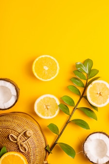 Summer bright yellow background with a straw bag, hat, oranges, lemon, coconut and a green branch. top view, flat lay