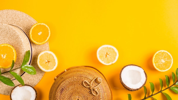 Summer bright yellow background with a straw bag, hat, oranges, lemon, coconut and a green branch