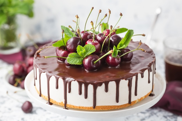 Summer cake with chocolate topping decorated fresh cherries on a white cake stand