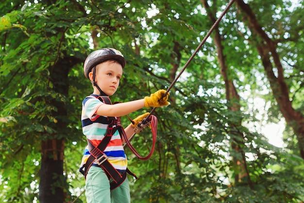 아이들을 위한 여름캠프. 나무 사이에서 높은 케이블 경로를 전달하는 아이.