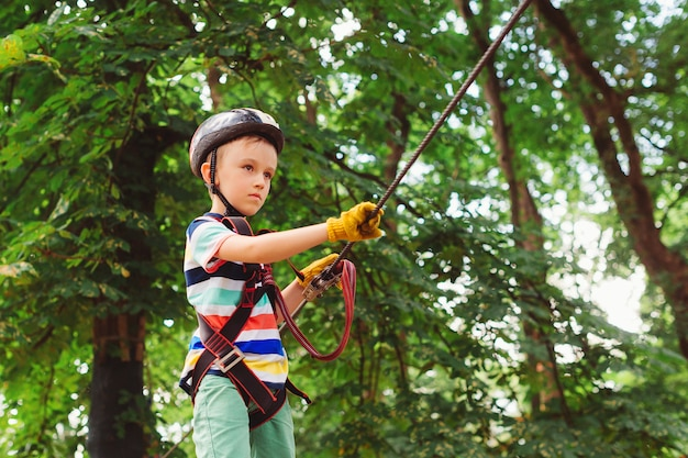 Summer camp for kids. child passing the cable route high among trees.